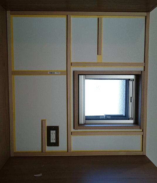 壁にマスキングテープと工作材を貼った所